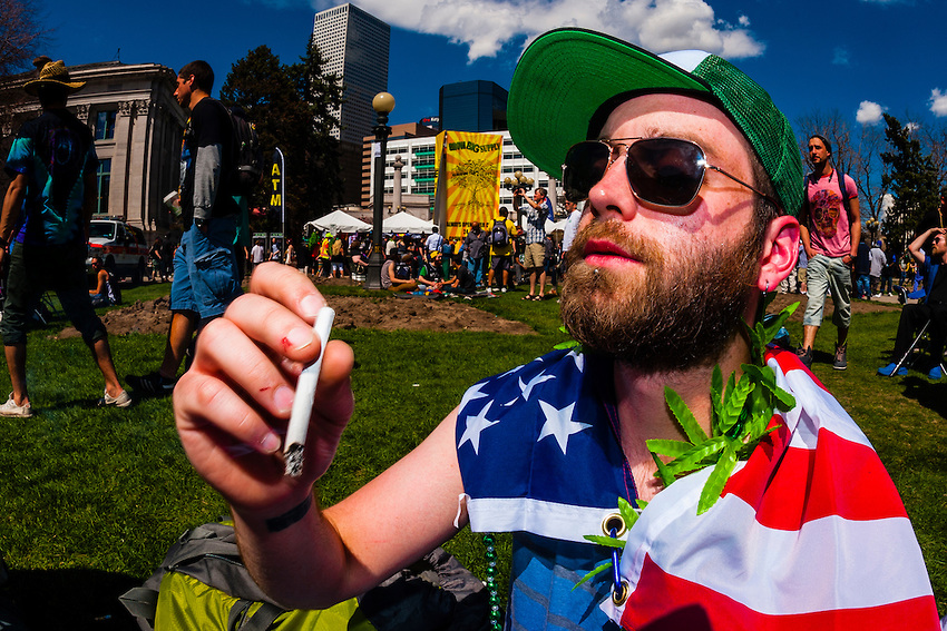 Smoking pot at the 420 Cannabis Culture Music Festival, Civic Center Park, Downtown Denver, Colorado USA. This was the first 4/20 celebration since recreational pot became legal in Colorado January 1, 2014. A crowd of up to 80,000 people attended the even