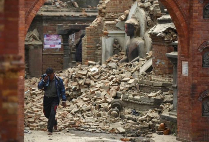 Man cries as he walks on the street while passing through a damaged statue of Lord Buddha a day after an earthquake in Bhaktapur