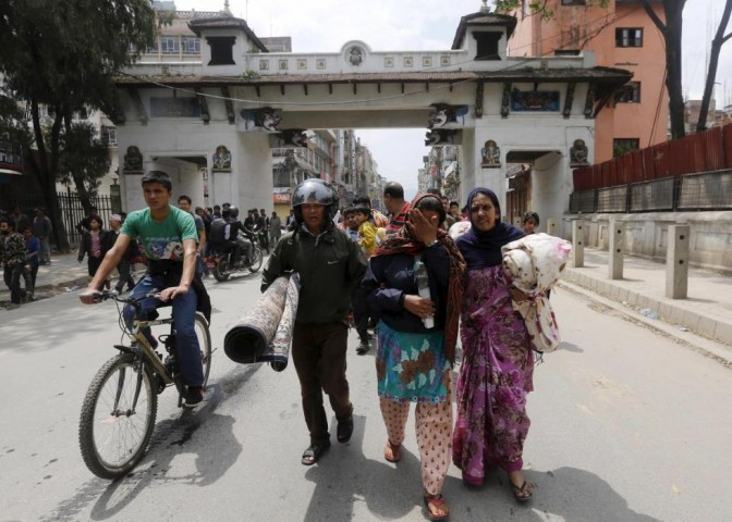 Family carry their belongings as they rush for safety during a strong aftershock after an earthquake, in Kathmandu