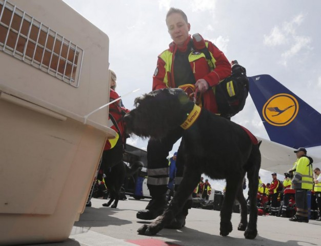 ISAR dog handler Martin-Schmitt  prepares her dog 'Porthos' to board their flight to Nepal from Frankfurt airport