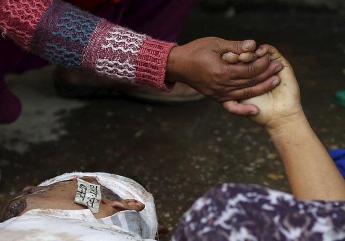 Woman holds the hand of a deceased relative who died during an earthquake outside a hospital in Kathmandu