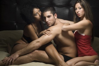 Man and Two Women in Bed Together