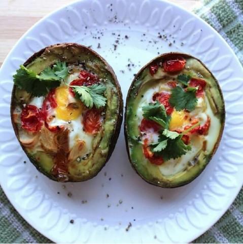 """Avokado un cepta ola -- Šādas ar proteīnu un """"labajiem"""" taukiem piesātinātas brokastis ļoti iepriecinās jūsu sirdi šī vārda tiešā nozīmē. Uzkarsējiet cepeškrāsni līdz 200 grādiem. Avokado pārgrieziet uz pusēm, izņemiet kauliņu un izdobjiet apmēram 2 karotes mīkstuma no katras pusītes. Iedobītēs ielejiet olu, pievienojiet tomātu, sāli un piparus. Cepiet apmēram 20 – 22 minūtes, pārkaisiet ar zaļumiem un mielojieties ar gardu muti."""